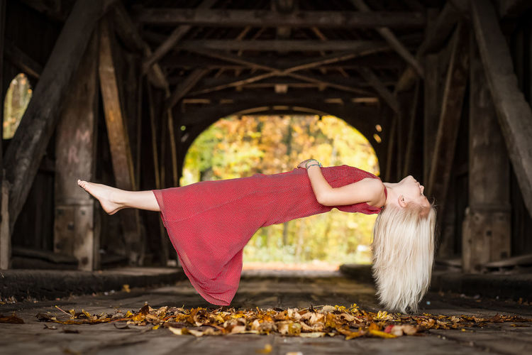 Full Length Of Woman Levitating Under Bridge