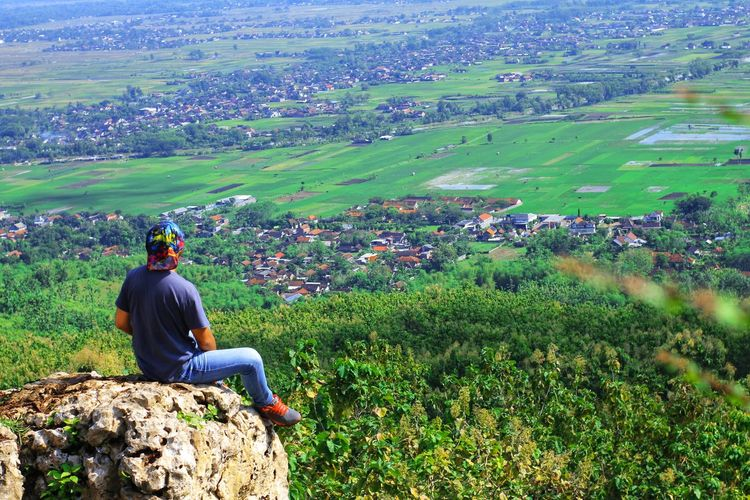 Full length of man looking at landscape while sitting on cliff