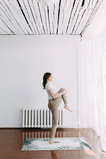 Side view of young woman standing on table against wall