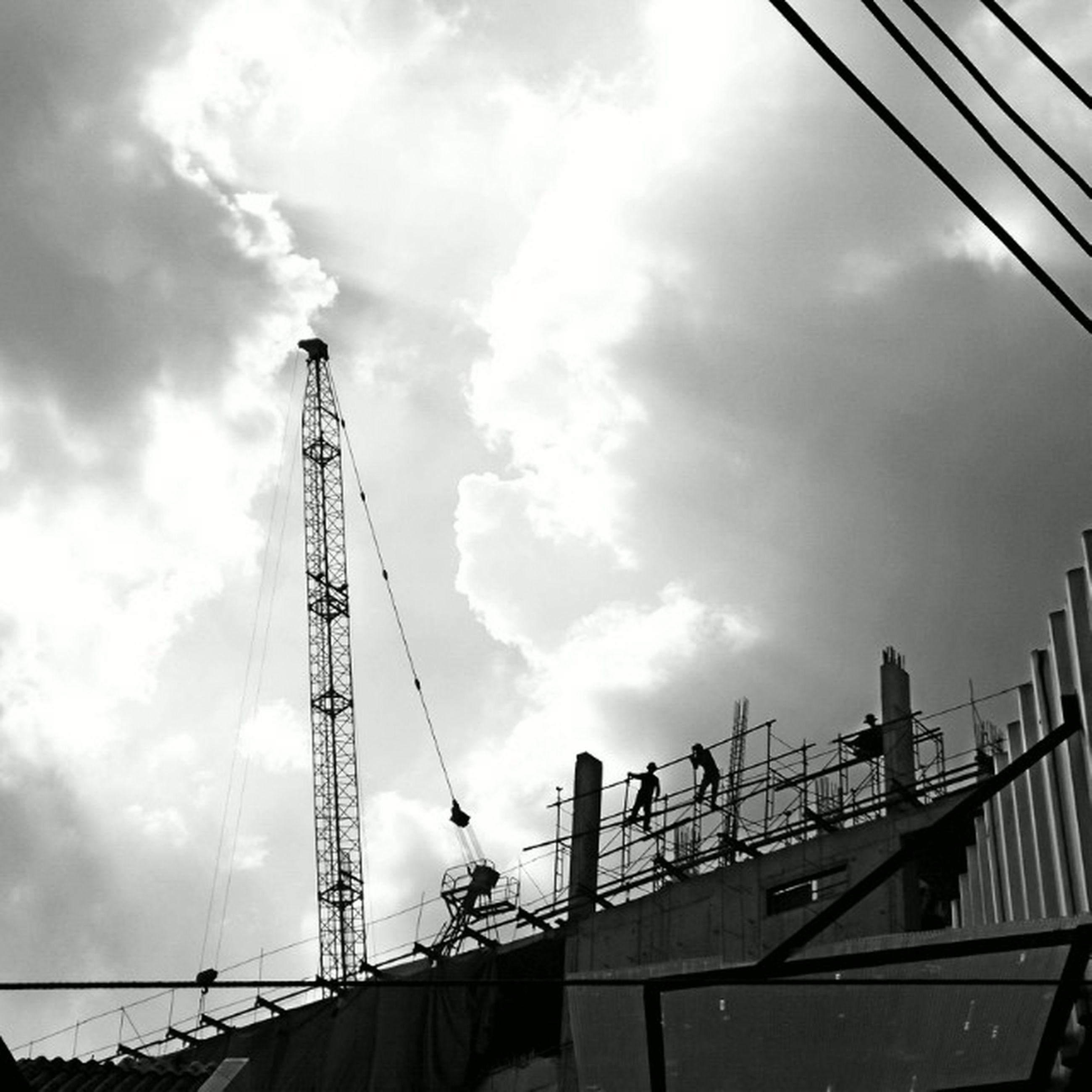 low angle view, sky, built structure, architecture, crane - construction machinery, construction site, connection, cloud - sky, development, building exterior, cloudy, cloud, construction, crane, industry, engineering, tall - high, outdoors, metal, day