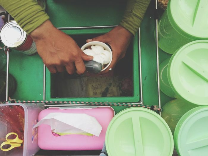 Cropped image of vendor filling coconut ice cream scoops in cup at concession stand
