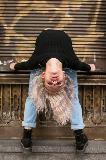 Portrait of young woman bending backwards against wall