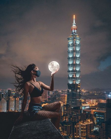 Full length of woman against illuminated buildings in city at night