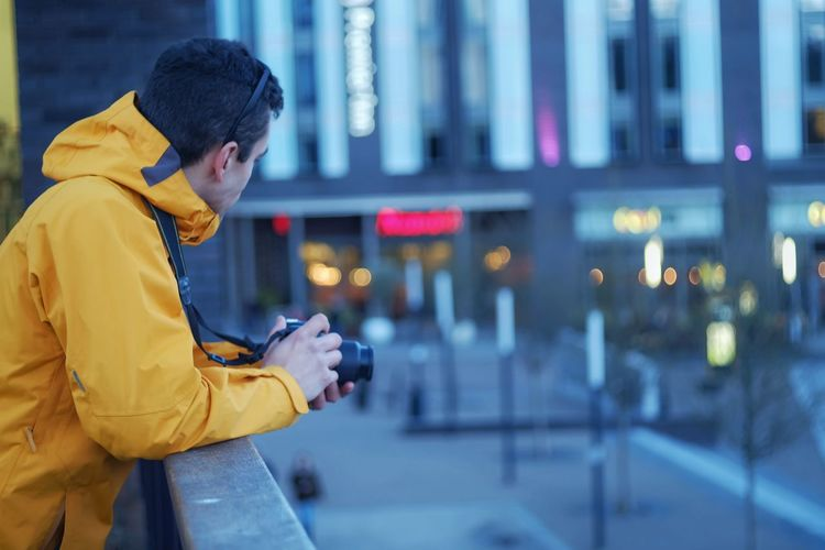 Side view of man holding digital camera while standing in city during sunset