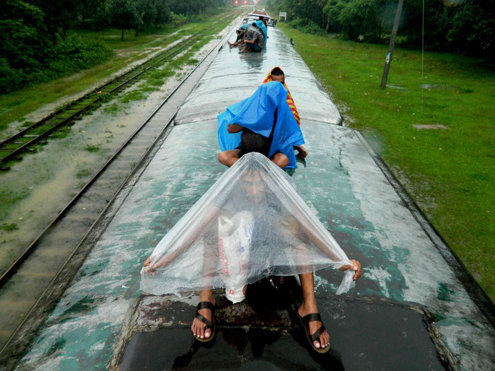 people are travelling on the roof of the train in rain. People Rain Train Transportation Travel Travelling On The Roof Of The Train. The Street Photographer - 2016 EyeEm Awards