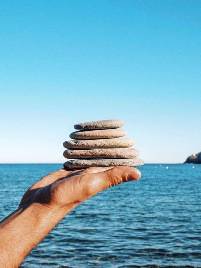 Cropped hand holding stacked rocks over sea against clear sky