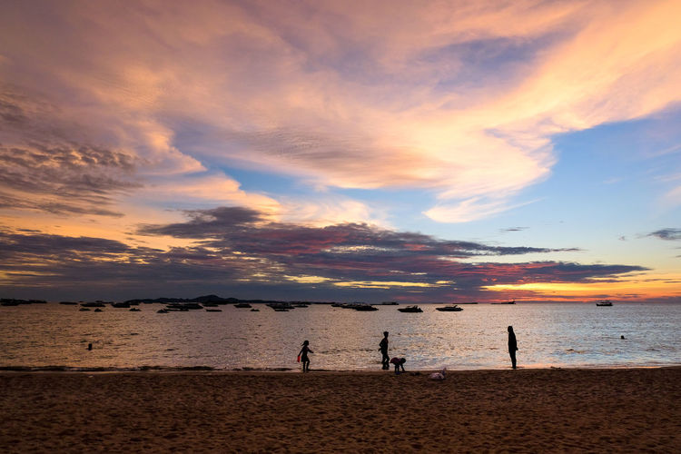 People playing on beach against sky during sunset