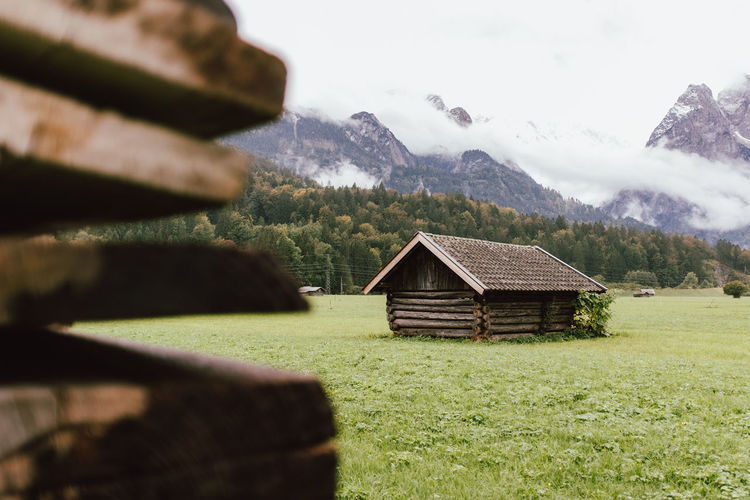 House on field against mountain
