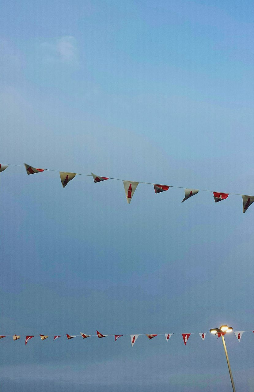 celebration, low angle view, cultures, in a row, sky, hanging, traditional festival, bunting, day, outdoors, spirituality, religion, multi colored, no people, cloud - sky, streamer, nature