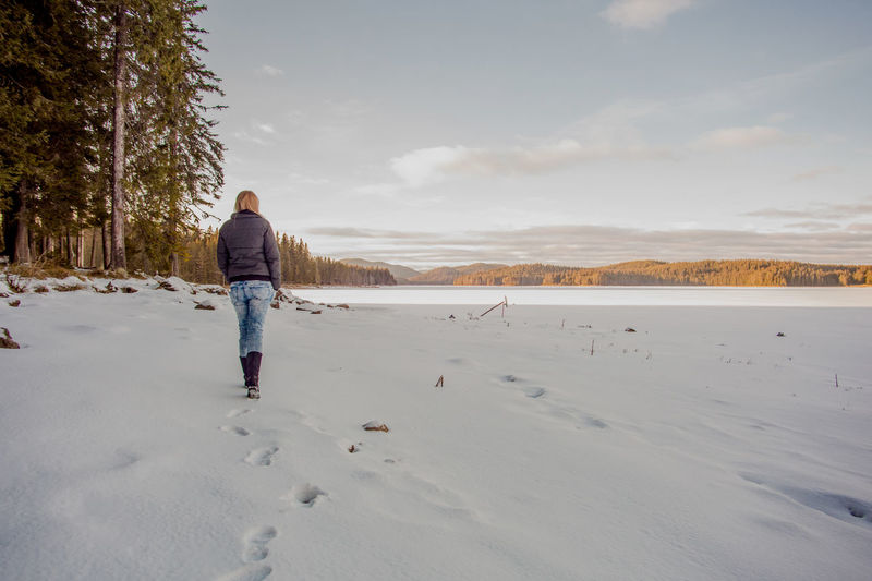 Rear view of woman walking on snowy landscape against sky