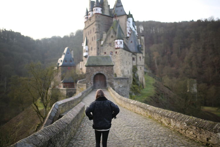 Burg Eltz Architecture Rear View Built Structure One Person Tree Day Building Exterior Nature Adult Leisure Activity Standing Bridge History Religion Real People Building Mountain Outdoors Burg Eltz Girl Woman Walking Winter Germany
