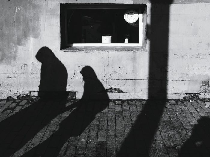 Shadow of man and woman sitting on wall