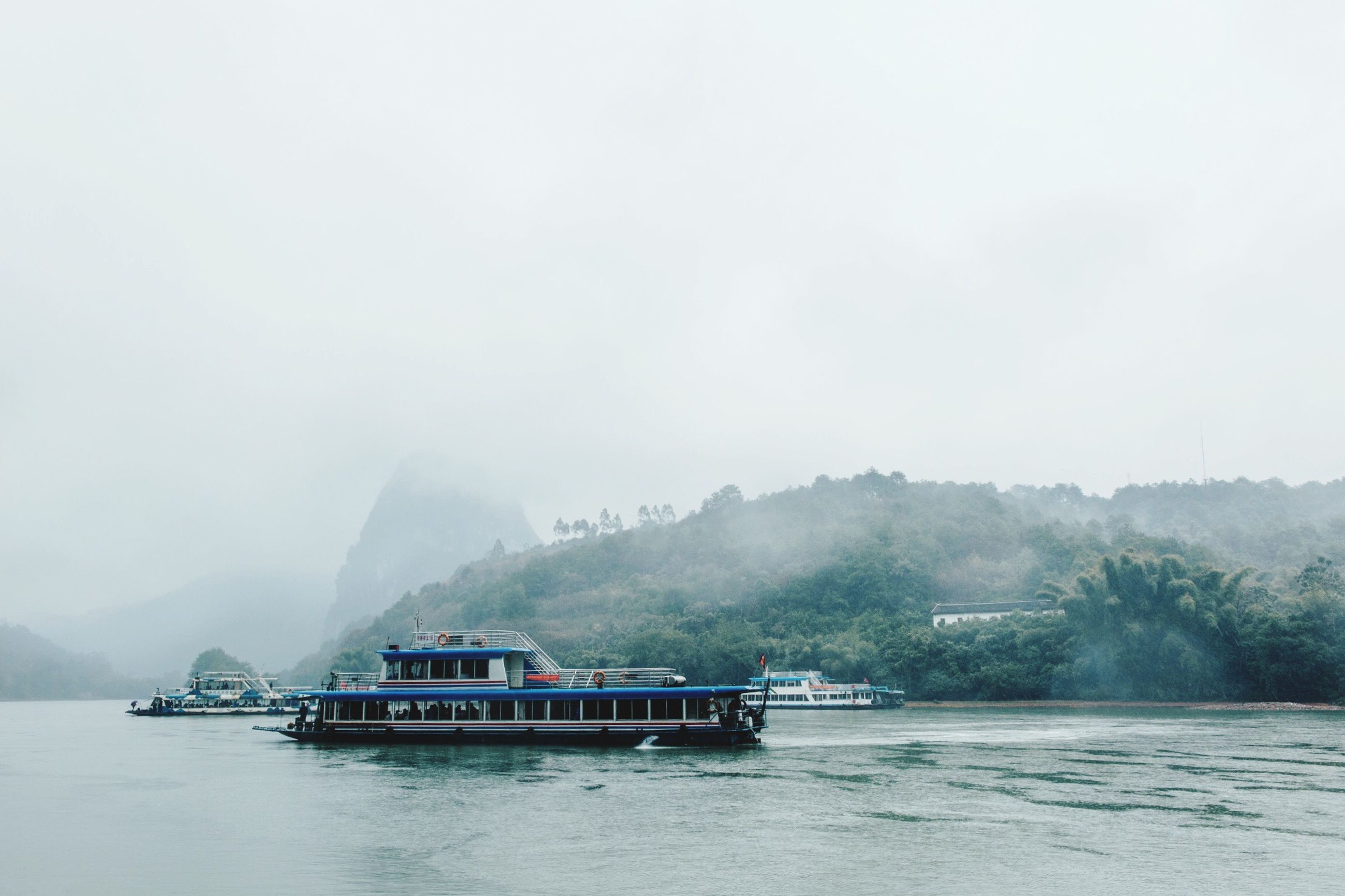 nautical vessel, mode of transport, nature, tranquil scene, fog, passenger craft, travel, beauty in nature, tranquility, tourism, water, environment, travel destinations, scenics, outdoors, boathouse, business finance and industry, mountain, ferry, sky, no people, architecture, day
