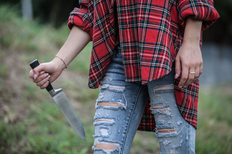 Midsection of woman in torn jeans walking with knife on field