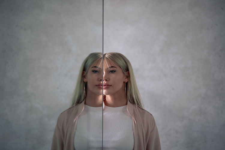 Young woman looking away while standing by mirror with reflection against wall