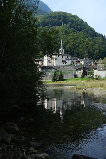House by lake and buildings against sky