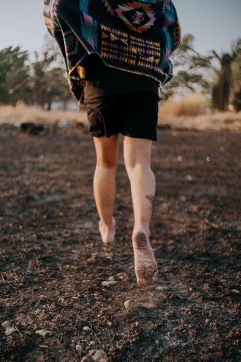 Low section of woman walking on field