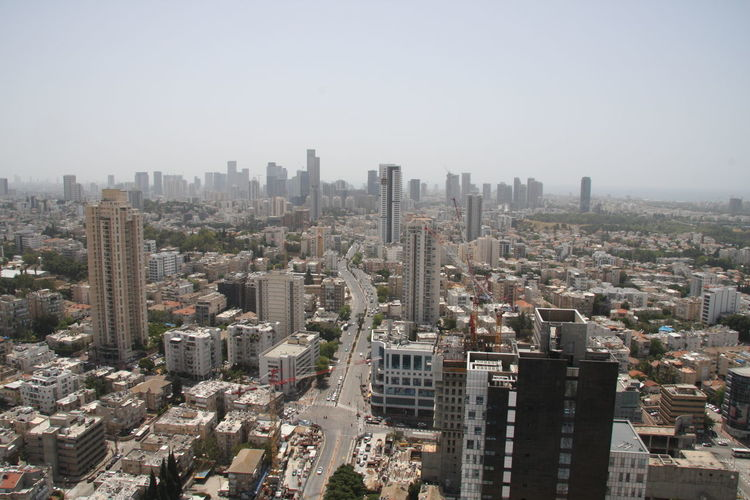 Aerial view of buildings in city against clear sky