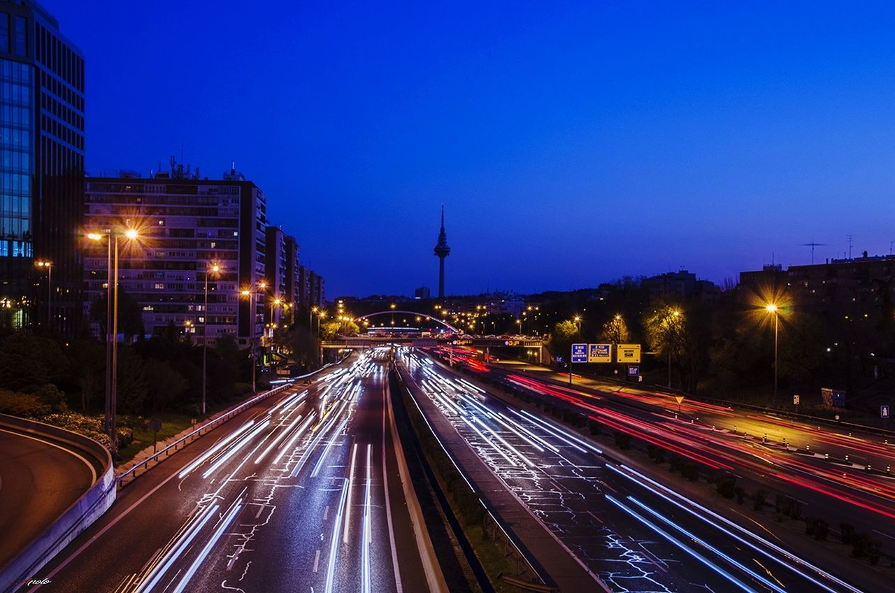 illuminated, night, light trail, long exposure, speed, motion, transportation, street light, high street, architecture, outdoors, road, building exterior, clear sky, no people, urban scene, built structure, blue, city, sky, cityscape