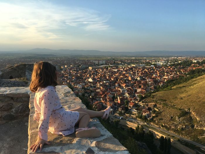Side view of girl looking at cityscape against sky during sunset