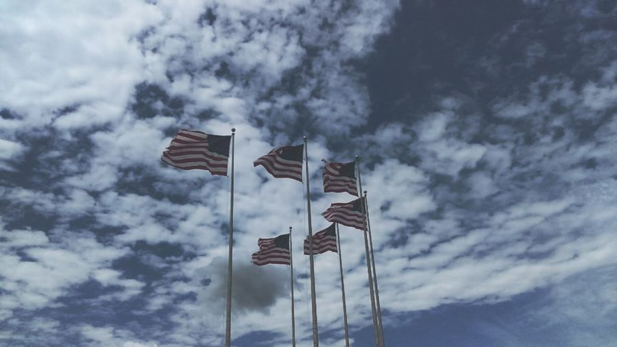 Low angle view of american flags against sky