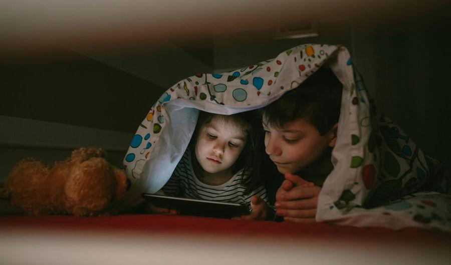 Siblings using digital tablet under blanket at home