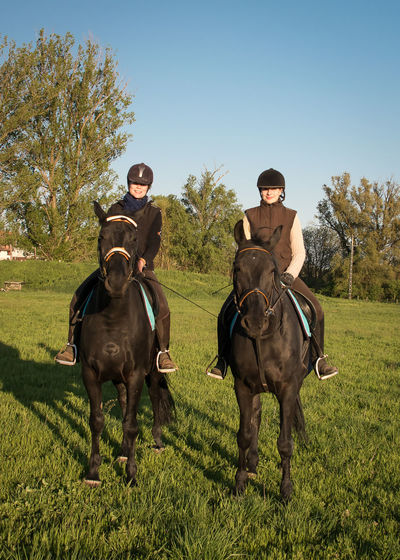 Female jockeys riding horses on grassy field against clear sky