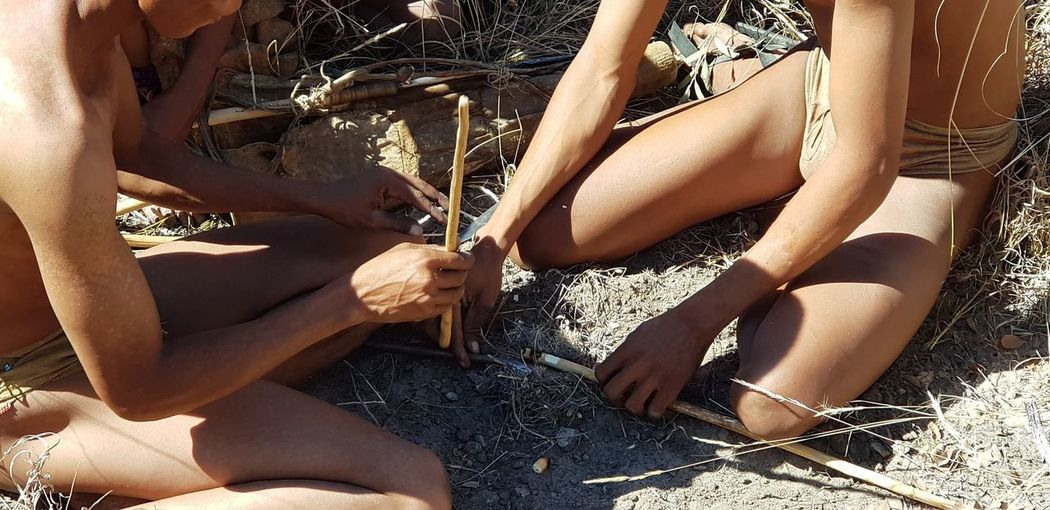 Ju|'hoansi San people using traditional method to start fire San People Tsumkwe Namibia Landscape Africa Tradition Traditional Clothing Traditional Culture Starting Fire Bushmen Ju|'hoansi EyeEm Selects Low Section Sitting Beach Shadow Human Leg Sunlight Sand High Angle View Thigh Knee Joint - Body Part Human Knee Human Joint Body Part
