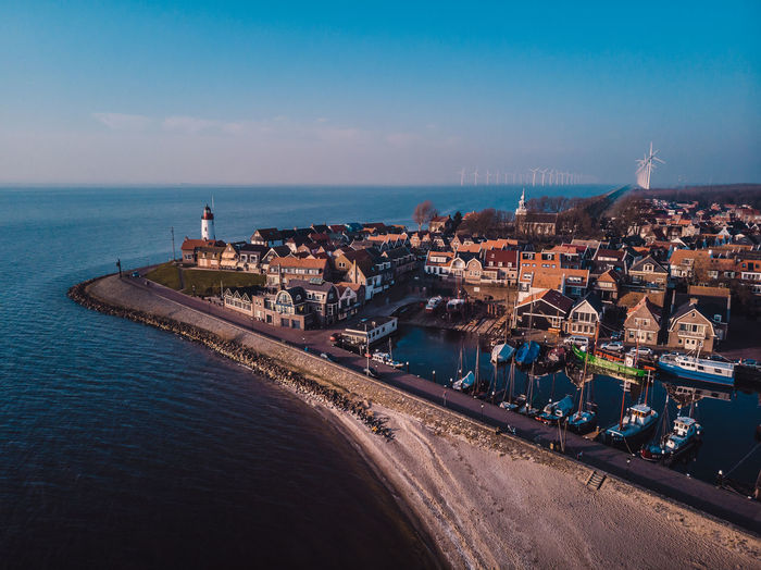 Aerial view of cityscape by sea against sky, lighthouse urk netherlands sunset