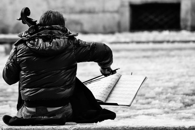 Rear view of musician playing double bass at street during winter