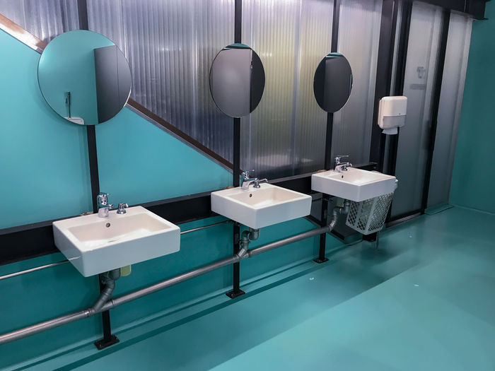 Several sinks with mirrors in a modern public toilet. Mirror Public Toilet Sinks Blue Clean Domestic Room Empty Green Color Hygiene Illuminated In A Row Indoors  Mirror No People Technology Turquoise Colored