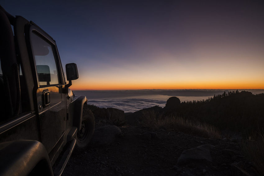 beautiful sunset on El Teide national park with offroad car and cloud sea El Teide National Parc Vacations Beauty In Nature Cloud Sea Environment Idyllic Land Land Vehicle Landscape Mode Of Transportation Nature No People Non-urban Scene Orange Color Outdoors Scenics - Nature Sea Sky Sunset Tenerife Tranquil Scene Tranquility Transportation Travel Destinations Water