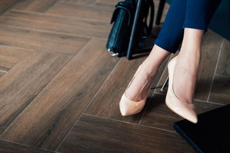 Low section of woman wearing high heels on hardwood floor