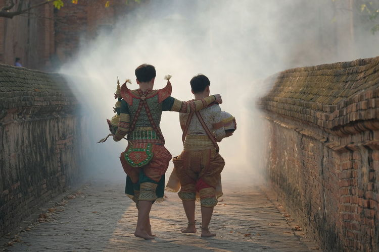 Rear view of men wearing traditional clothing walking outdoors