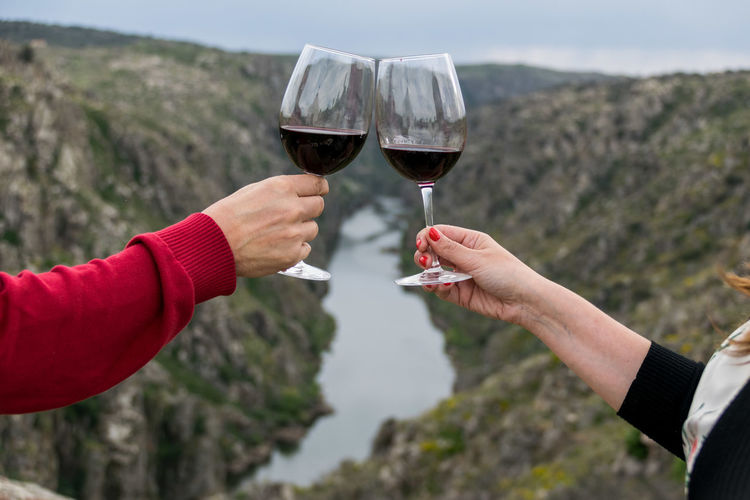 Close-up of hand holding drink against mountain
