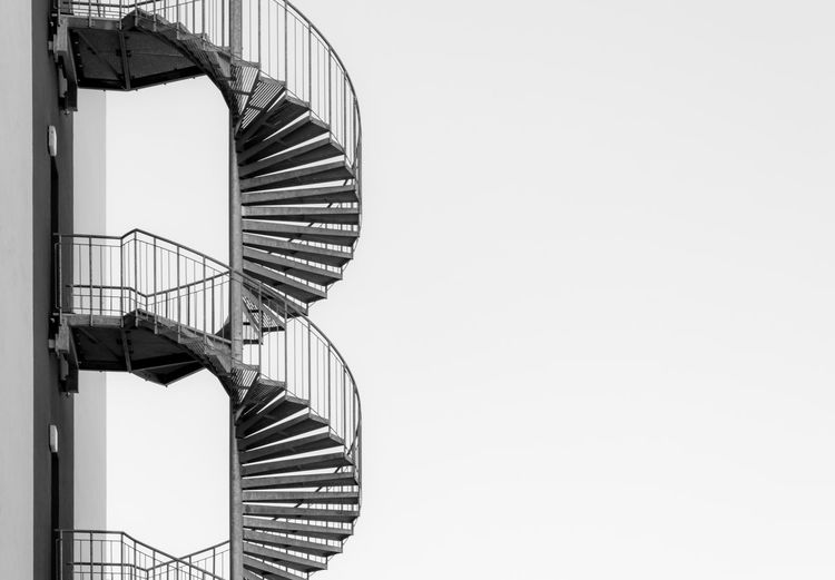 Spiral Staircase By Wall Against Clear Sky