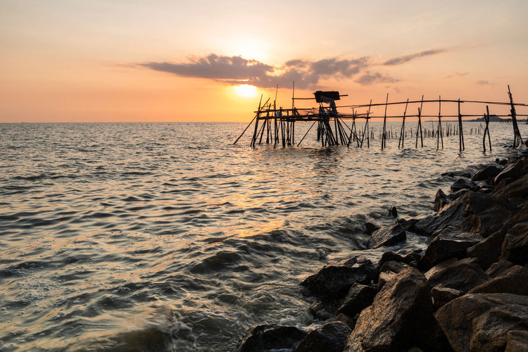Wooden jetty at the rocky seaside during sunset. Sunset Sky Water Sea Scenics - Nature Beauty In Nature Orange Color Horizon Over Water Cloud - Sky Tranquil Scene Tranquility Horizon Idyllic Beach Nature Silhouette Land No People Outdoors Golden Hour Seascape Ocean Wave Rock