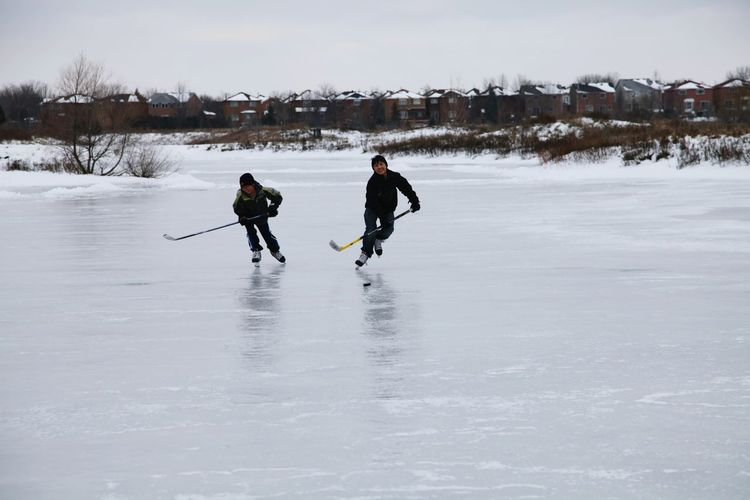Canadian pond hockey Winter Winter Sport Snow Two People Cold Temperature Full Length Ice Hockey Hockey People Day Adult Outdoors Ice Rink Adults Only