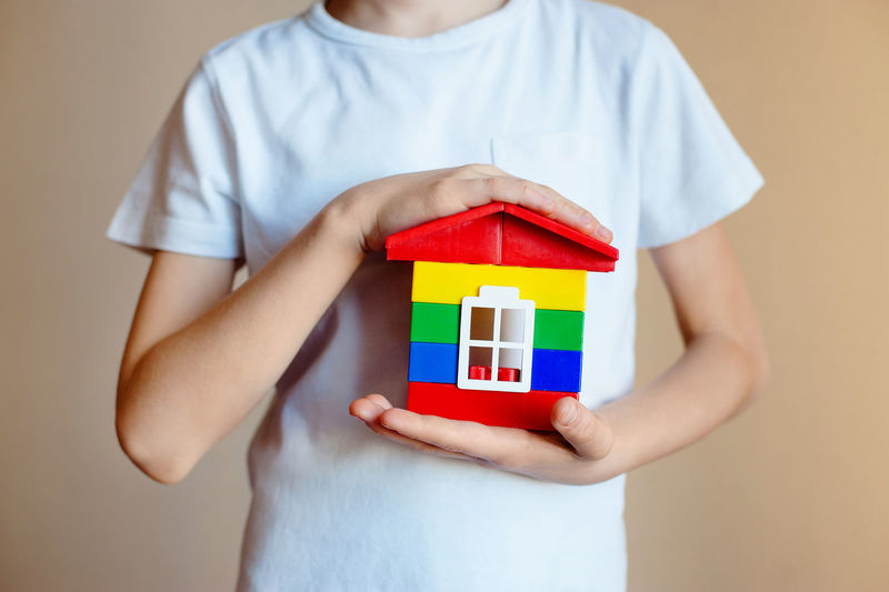 Boy Holding Toy House
