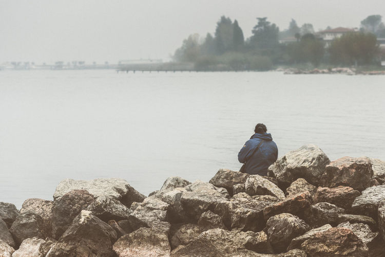 Rear view of woman sitting on rocks at lakeshore
