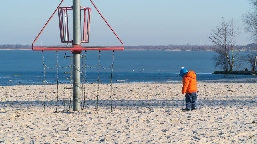 Rear view full length of boy standing by structure at beach