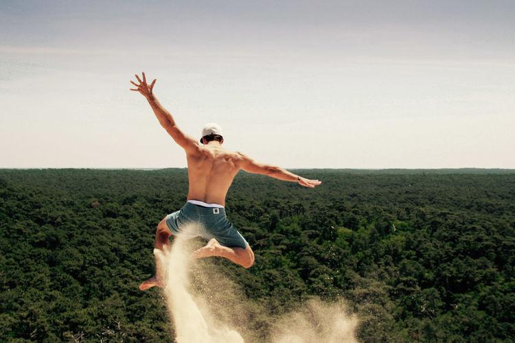 Full length of shirtless man jumping over landscape against sky