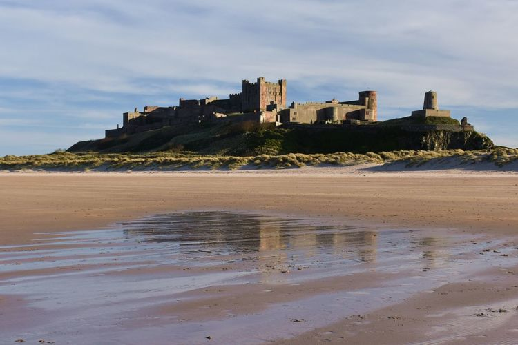 Looking up at Bamburgh Castle from the beach Water Built Structure Architecture Land Sky Building Exterior Beach Sand Sea Nature Building Cloud - Sky Castle History The Past Day No People Outdoors Bamburgh Bamburgh Castle Castle Castle View  Historic Historical Building Sandy Beach Reflection Reflections Blue Sky Sunlight Backgrounds Scenics Coastline Coast Coastal Feature Background View Dunes Evening Evening Light