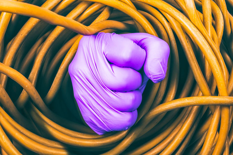 Full Frame Shot Of Tangled Yellow Cable With Purple Hand