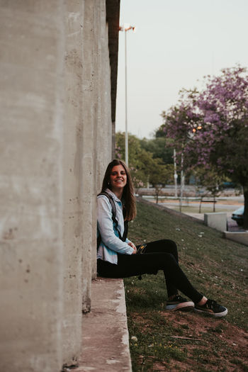 Portrait of woman sitting on wall