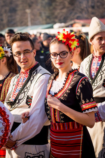 PERNIK, BULGARIA - JANUARY 26, 2018: Couple dancers in Bulgarian folklore costumes hold arms during ritual march at the sunny winter day at the annual International Festival of Masquerade Games Surva Beautiful Event Games Kukeri Kukeri, Bulgaria Beauty Celebration Day Event Festival Focus On Foreground Lifestyles Looking At Camera Masquerade Outdoors Portrait Real People Smiling Surva Togetherness Traditional Clothing Young Adult Young Women