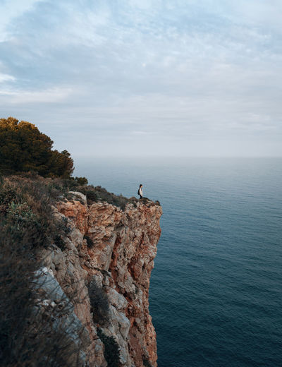 Scenic view of woman standing on cliff against sea and sky