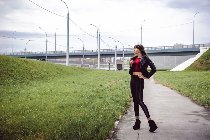 Thoughtful Young Woman Standing On Footpath By Field With Bridge In Background