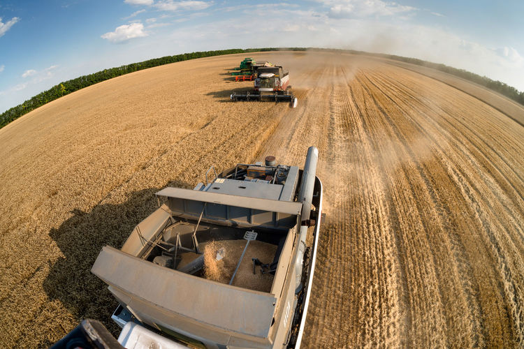 High Angle View Of Combine Harvester On Wheat Field Against Sky