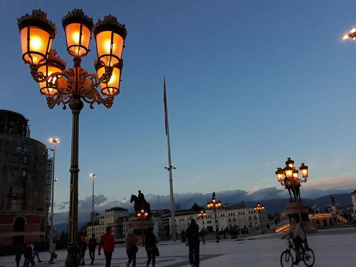 People at illuminated street light against sky
